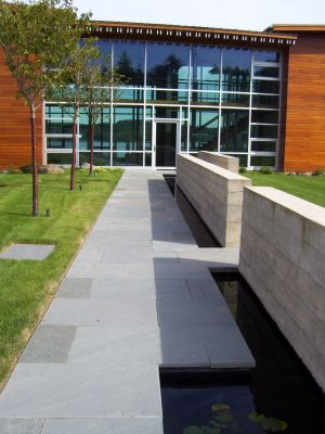 A strong axis created by the walls and entry path bordering a water feature is mirrored by an allee of cherry trees